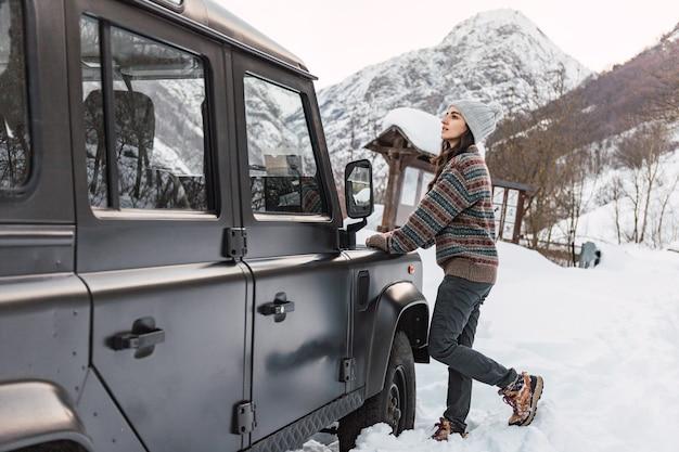 イタリアアルプスで彼女の車にもたれて雪に覆われた山を見ている少女。