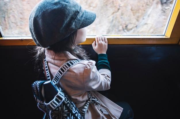 列車の窓を見る少女