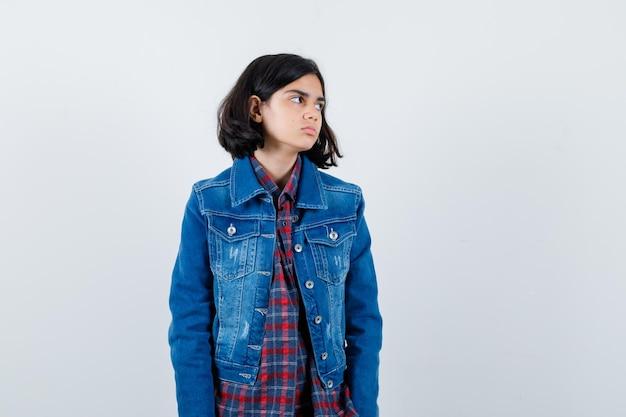 Giovane ragazza che guarda lontano mentre posa alla macchina fotografica in camicia a quadri e giacca di jeans e sembra carina, vista frontale.