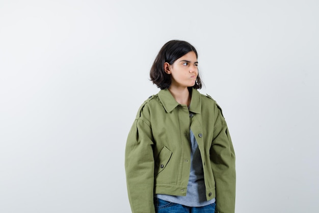 Giovane ragazza che guarda lontano mentre posa in maglione grigio, giacca kaki, pantaloni jeans e sembra seria, vista frontale.
