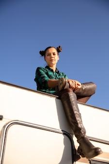 Giovane ragazza che guarda in basso e seduta sul tetto di un camper retrò. cielo blu