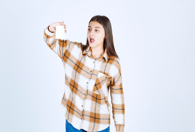 Young girl looking at empty cup on white wall.