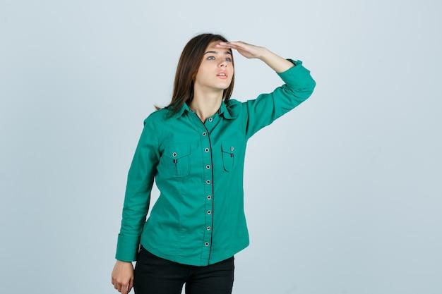 Ragazza che guarda lontano con la mano sopra la testa in camicetta verde, pantaloni neri e guardando concentrato. vista frontale.