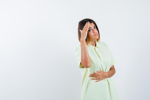 어린 소녀 t- 셔츠에 머리 위로 손으로 멀리보고 집중, 전면보기를 찾고.