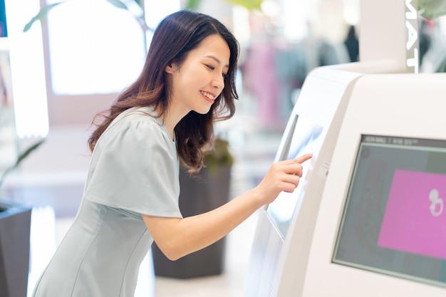 ショッピングモールで電子機器の情報を探している少女