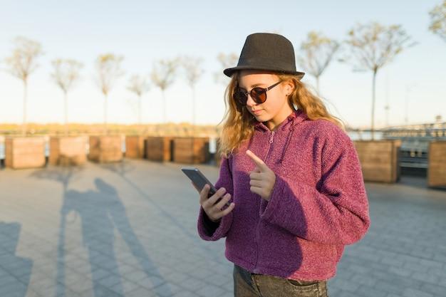 Молодая девушка смотрит в мобильный телефон и показывает указательный палец вверх