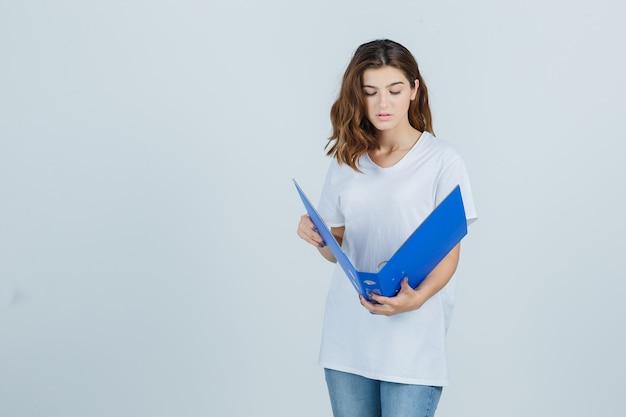Молодая девушка смотрит в папку в белой футболке и смотрит сосредоточенно. передний план.