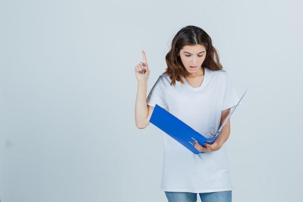 Молодая девушка смотрит в папку, указывая вверх в белой футболке и выглядит удивленным. передний план.