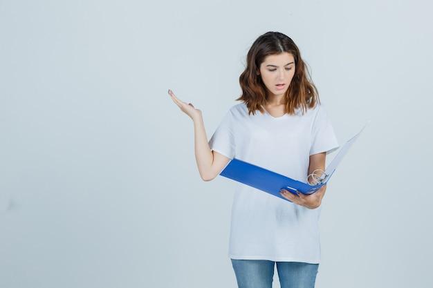 Молодая девушка смотрит в папку, поднимая руку в белой футболке и разочарованно глядя, вид спереди.