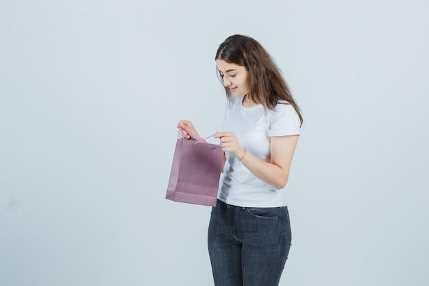 Ragazza che esamina un sacchetto di carta in maglietta, jeans e che sembra pensieroso.