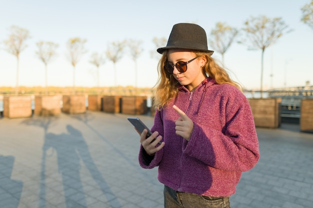 Young girl looking in mobile phone and showing index finger up
