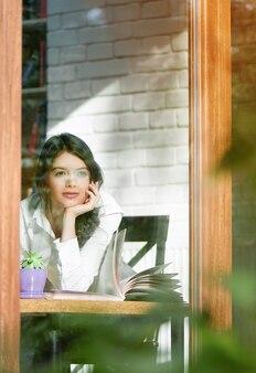 Молодая девушка, глядя за пределы окна стекла