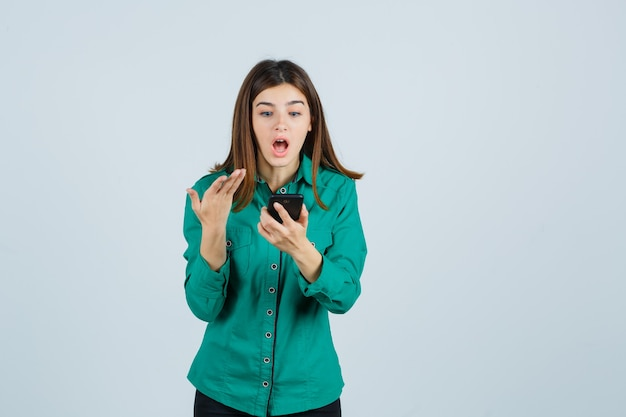 Young girl looking at phone, stretching hand toward it in surprised manner in green blouse, black pants and looking shocked , front view.
