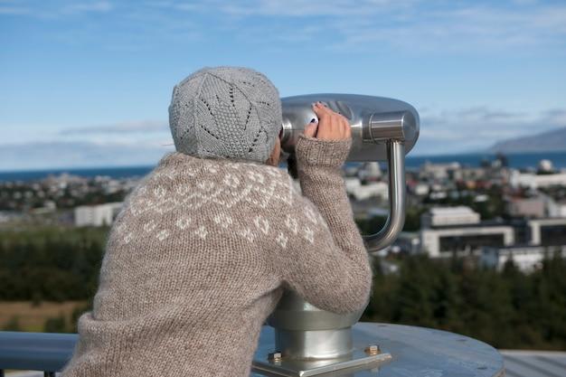 Молодая девушка, глядя через бинокль телескопический зритель в cityscape