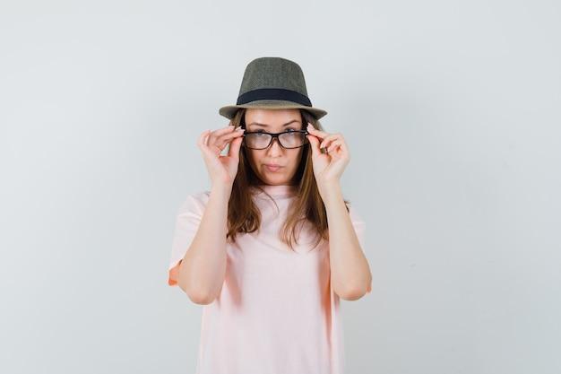 ピンクのtシャツ、帽子、躊躇して眼鏡を通して見ている少女。正面図。