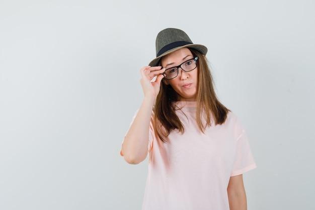 Ragazza giovane guardando attraverso gli occhiali in t-shirt rosa, cappello e guardando indeciso, vista frontale.