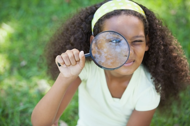 어린 소녀는 공원에서 돋보기를 통해 보이는