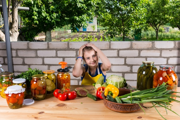 疲れているように見え、手で頭を抱え、新鮮な野菜と漬物の瓶に囲まれたテーブルに座っている少女は、屋外の庭で保存します
