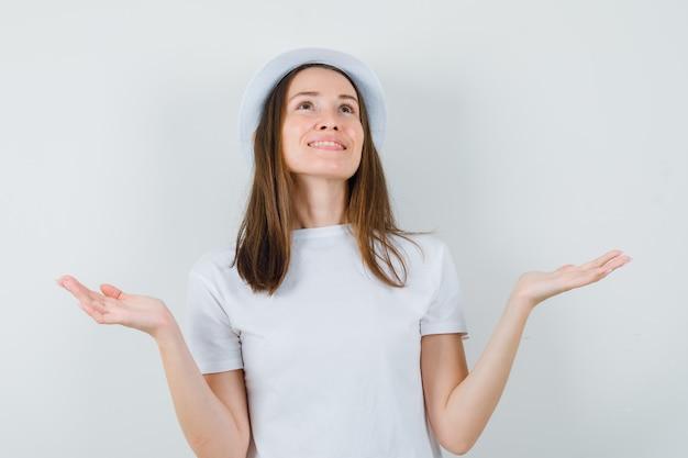 Молодая девушка смотрит вверх, разводит ладони в белой футболке, шляпе и выглядит благодарным, вид спереди.