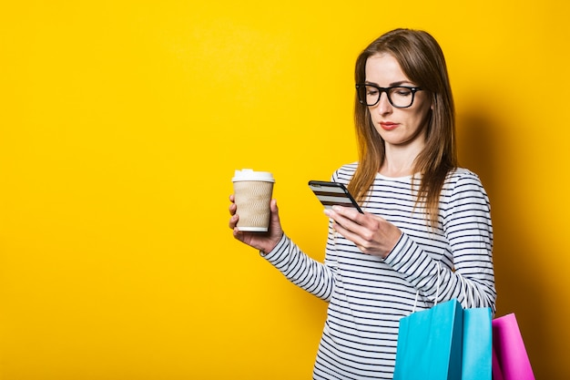 Молодая девушка смотрит в телефон, с бумажным стаканчиком с кофе и с пакетами с покупками на желтом фоне