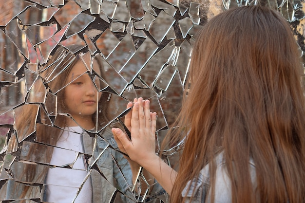 Young girl looks in a broken mirror and shows her hand on a mirror.