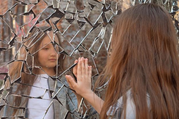 Молодая девушка смотрит в разбитое зеркало и показывает руку на зеркало.