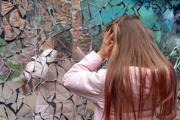 若い女の子は壊れた鏡を見て苦しみ、頭を抱えています。人間の感情の概念。