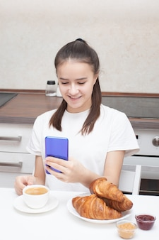 Young girl looks at a smartphone, communicates via video calling at breakfast