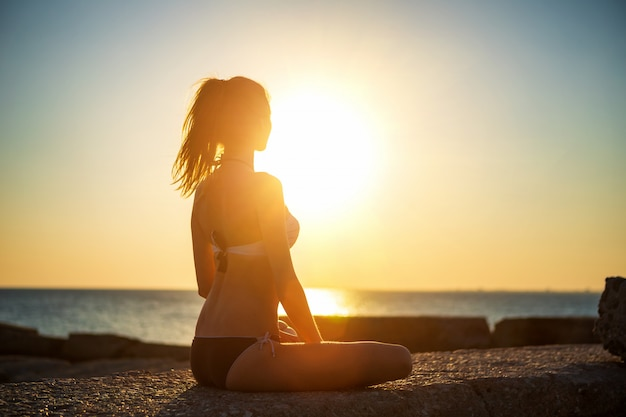 Young girl in lotus position by the sea at sunset