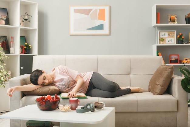 거실에 있는 커피 테이블 뒤에 소파에 누워 자는 어린 소녀