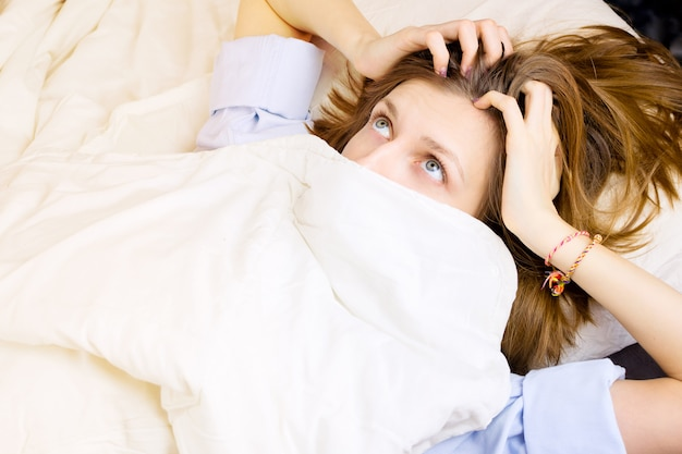 Young girl lying in her bed, face covered by blanket with eyes wide open with surprise. , morning or night sleep concept.