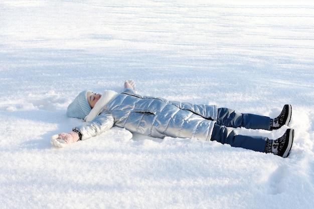 Молодая девушка, лежа на снегу и наслаждаясь моментом жизни. зимние подвижные игры