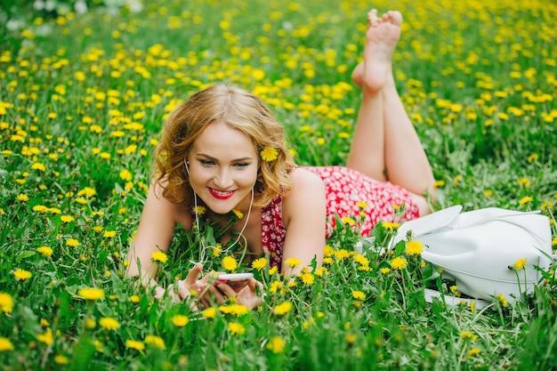 Молодая девушка лежит на поле среди одуванчиков и слушает музыку