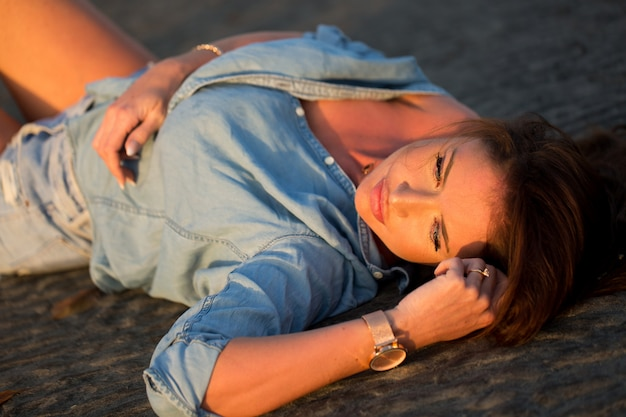 Young girl lying on the sand at sunset