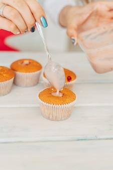 Young girl makes delicious tender cupcakes.