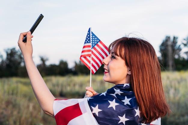Молодая девушка делает автопортрет, празднует день независимости и развлекается с национальным флагом сша. 4 июля