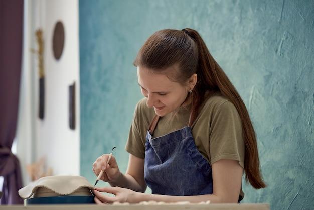 Маленькая девочка делает керамическую миску в классе. концепция творческого хобби