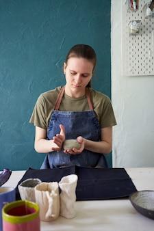 Молодая девушка делает керамический горшок, месить глину в руках. концепция творческого хобби