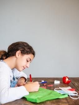 Молодая девушка делает поделки на деревянном столе
