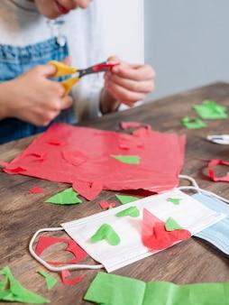 Молодая девушка делает поделки из бумаги и ножниц, лица не показаны, только руки