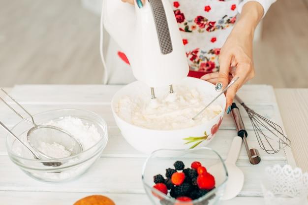 カップケーキのクリームを作る少女。