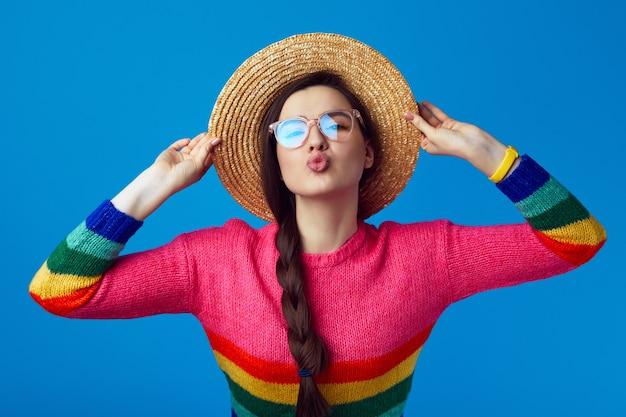 Молодая девушка делает поцелуй в губы в соломенной шляпе и очках с радужным свитером