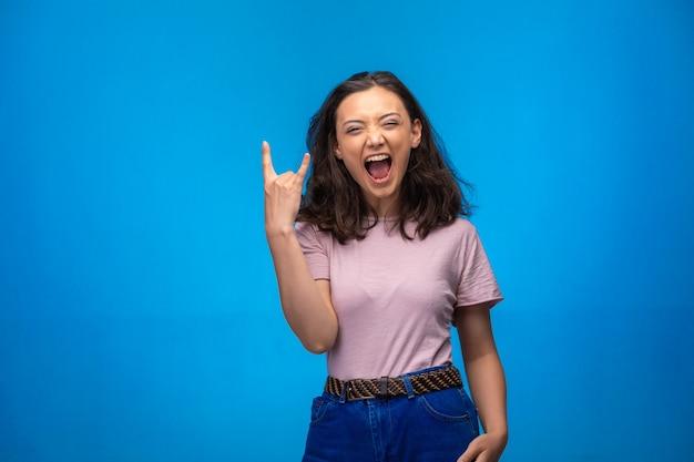 Молодая девушка делает символ мира пальцами и положительно смеется.