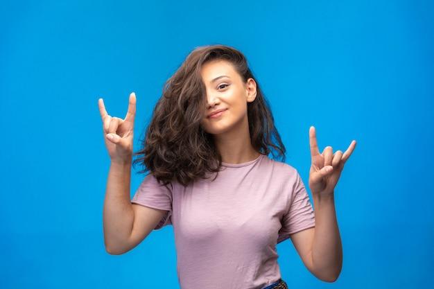 指で平和のシンボルを作るとかなり笑顔の少女。