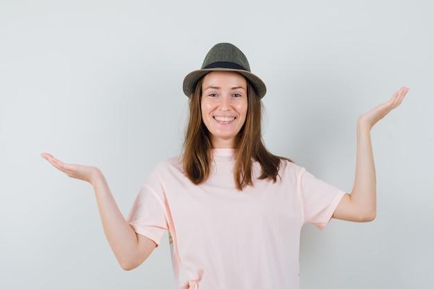 ピンクのtシャツ、帽子で体重計のジェスチャーを作っている若い女の子と陽気に見える、正面図。
