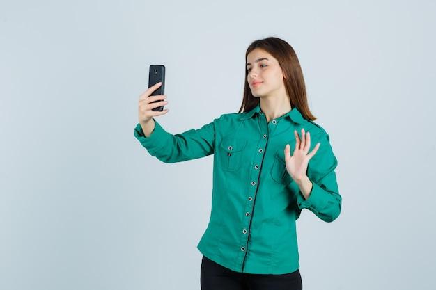 ビデオハングアウトをしている若い女の子、緑のブラウス、黒のズボンで挨拶するために手を振って、陽気に見える、正面図。