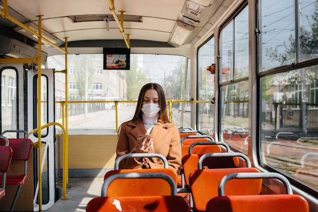 A young girl in a mask uses public transport alone, during a pandemic. protection and prevention covid-19.