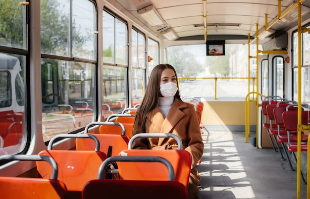 A young girl in a mask uses public transport alone, during a pandemic. protection and prevention covid 19.