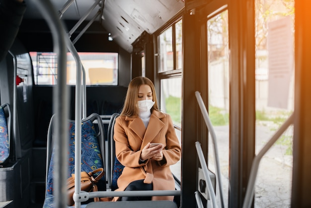 Young girl in mask uses public transport alone, during pandemic.
