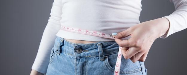 Young girl measures abdominal girth on a gray wall